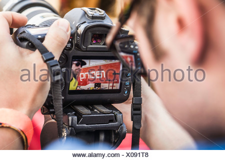 Close up of photographer checking photograph of mountain biker on camera - Stock Photo