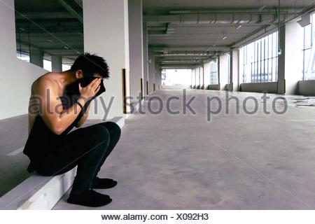 Side View Of Man Covering His Face With T-Shirt - Stock Photo