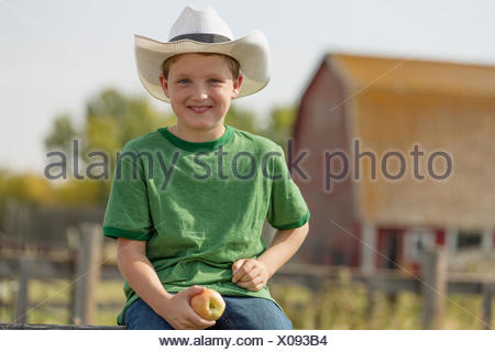 Young boy with cowboy hat sitting on fence. - Stock Photo