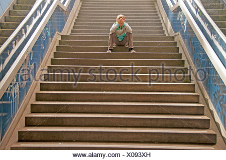 Lonely boy sitting on a staircase - Stock Photo