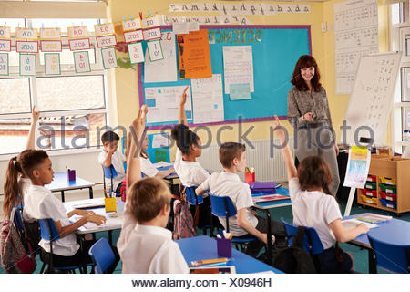 Primary school kids raising hands in class to answer teacher - Stock Photo