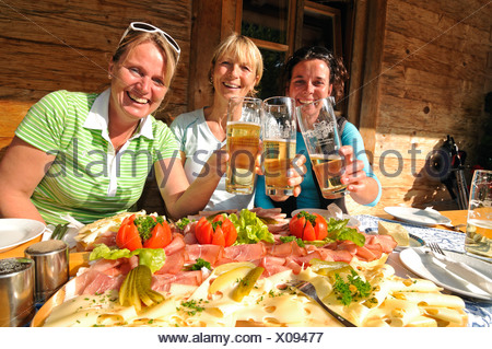 Women having a snack platter and beer after a hike - Stock Photo
