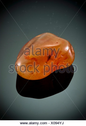 Cutout of a Carnelian (also spelled cornelian) gemstone on black background - Stock Photo