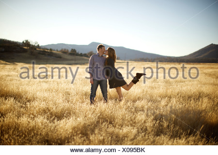 Female approaches male for a kiss in an open field. - Stock Photo