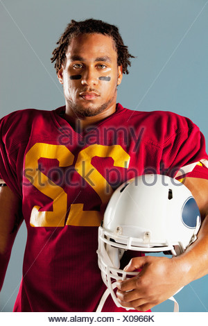 Football player holding helmet - Stock Photo