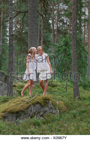 Teenage girls standing on rocks in forest - Stock Photo