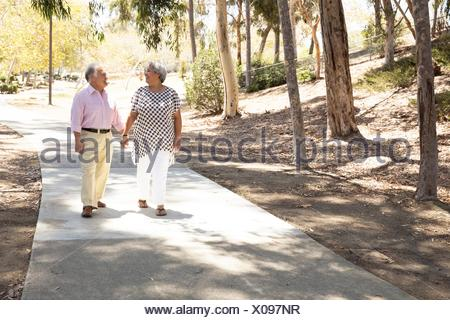 Senior couple walking hand in hand, outdoors - Stock Photo