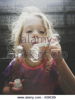 Portrait of a Girl blowing soap bubbles - Stock Photo