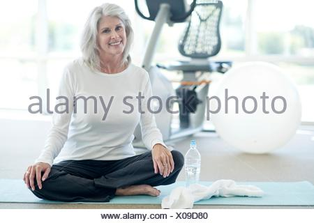 Senior woman sitting cross legged in gym. - Stock Photo