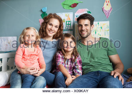 Family picture of couple with her little daughters sitting together on bed in children's room - Stock Photo