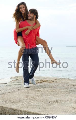 Young man giving girlfriend piggyback ride, portrait - Stock Photo