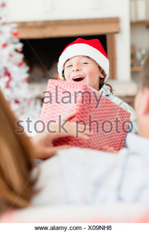 Boy in Santa hat with Christmas gifts - Stock Photo