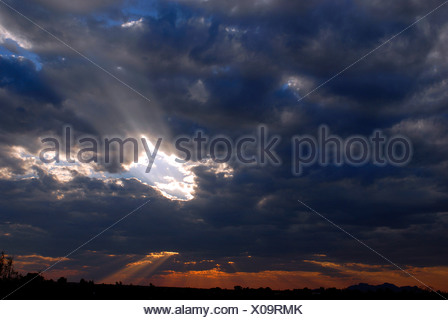 sunbeams braking through black thunderclouds over the outback, Australia, Yulara - Stock Photo