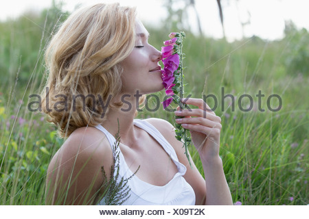 Netherlands, Gelderland, Hatertse Vennen, Portrait of happy woman with purple flower - Stock Photo