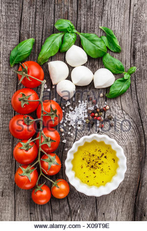 Cherry tomatoes, basil leaves, mozzarella cheese and olive oil for caprese salad - Stock Photo