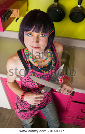 Brightly dressed punk woman with knives in a colorful kitchen - Stock Photo