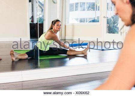 Mid adult woman stretching in front of mirror - Stock Photo
