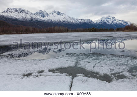 The Chugach Mountains are reflected in Mirror Lake State Wayside Park, Anchorage, Alaska. - Stock Photo