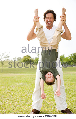 father holding son upside down in the park - Stock Photo