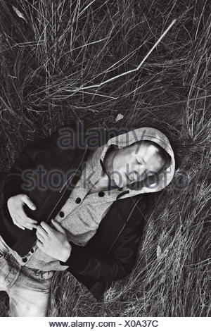 Man lying down in grass - Stock Photo