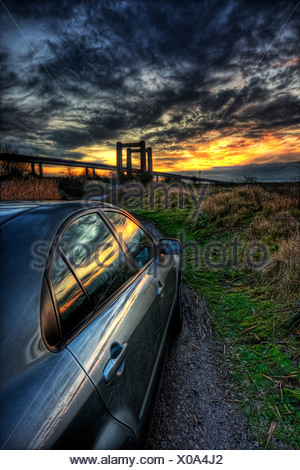 Evening sunset over the river swale reflected in the side of a shiny car with the new and old swale bridges on the horizon - Stock Photo