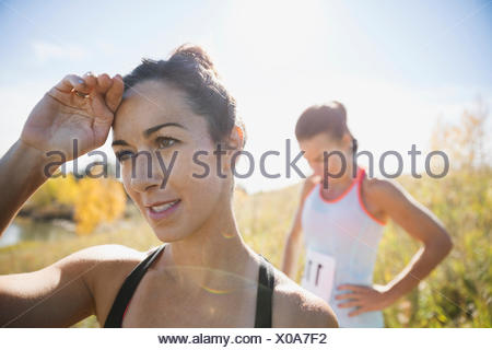 Runners resting in sunny field - Stock Photo