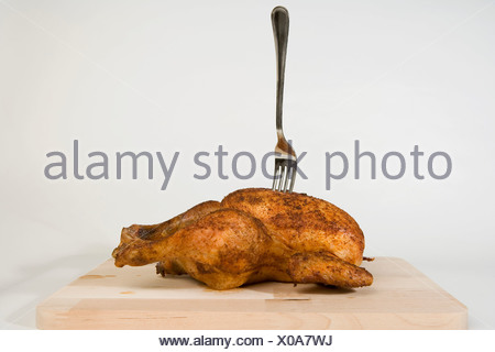 A fork stuck in a roast chicken - Stock Photo
