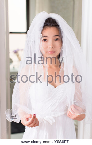 Young woman wearing wedding dress with veil - Stock Photo