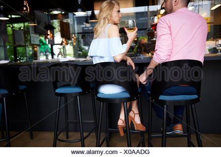 Rear view of man touching angry young woman's knee at bar - Stock Photo