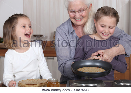 grandmother and granddaughters making pancakes - Stock Photo