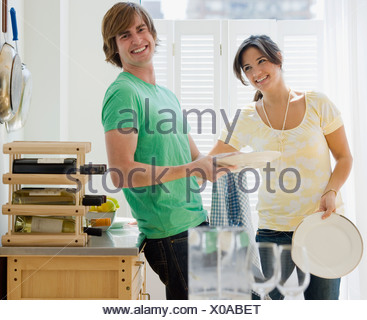 Couple washing dishes in kitchen - Stock Photo