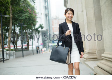 Businesswoman carry a bag and leaving office - Stock Photo