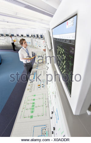 Engineer looking up at computer monitor in control room of nuclear power station - Stock Photo