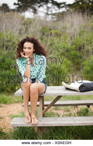Young woman sitting on picnic table smiling, portrait - Stock Photo