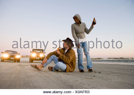 Young interracial couple holding beer bottle on beach in front of cars - Stock Photo