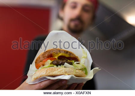 Young man serving hamburger from fast food van - Stock Photo