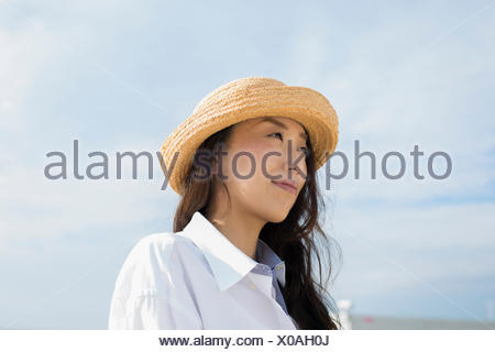 A woman in a straw hat on a beach in Kobe. - Stock Photo
