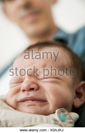 Young father holding his crying newborn son - Stock Photo