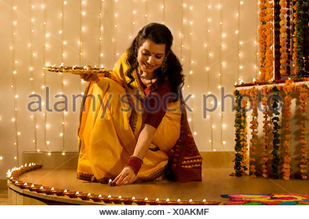 Woman arranging diyas - Stock Photo
