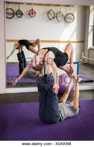 Young couple practicing acro yoga - Stock Photo