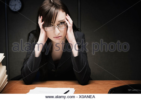 Stressed businesswoman at desk - Stock Photo