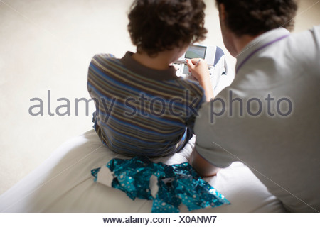 Father watching son play Christmas video game - Stock Photo