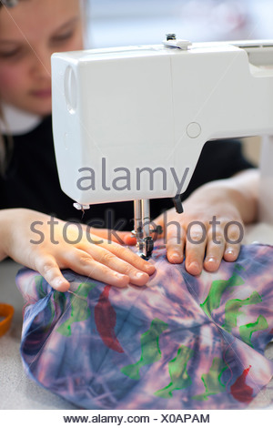 Close up of girl using sewing machine in classroom - Stock Photo