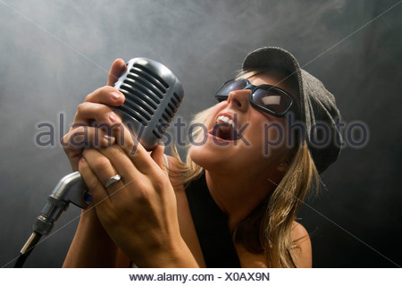 Woman singing in a microphone - Stock Photo
