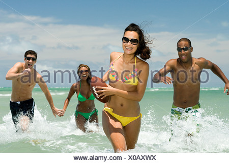 Friends running in sea with football - Stock Photo
