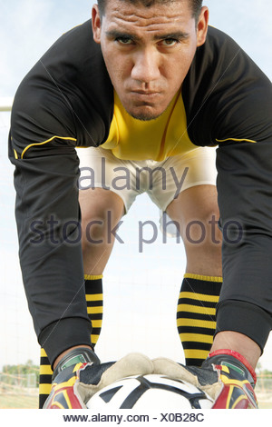 Goalkeeper bending down with ball, portrait - Stock Photo