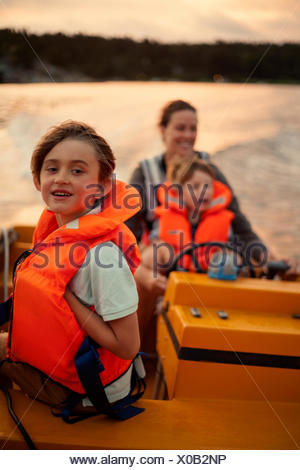Sweden, Uppland, Runmaro, Barrskar, Mother with sons (4-5, 6-7) on motorboat - Stock Photo