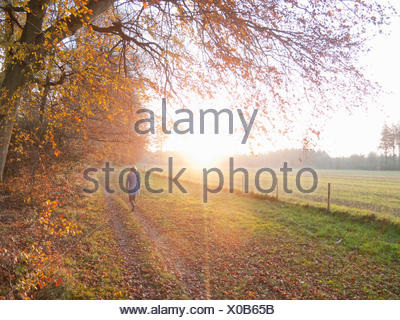 Woman walking in countryside in the autumn - Stock Photo