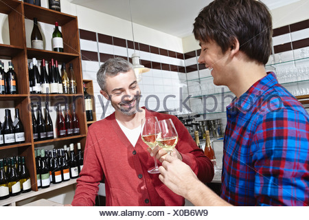 Germany, Cologne, Man having wine, smiling - Stock Photo