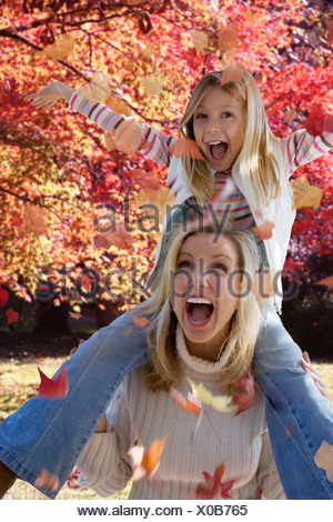 Mother and daughter playing in autumn leaves - Stock Photo